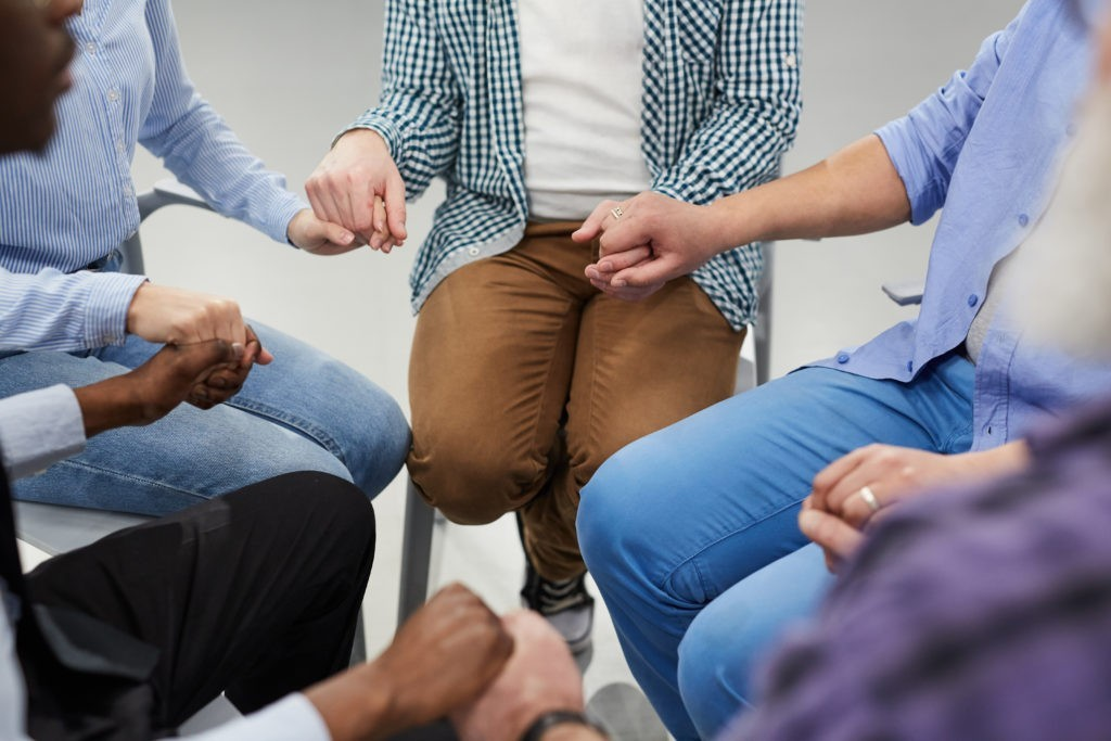 People holding hands sitting in circle during therapy session